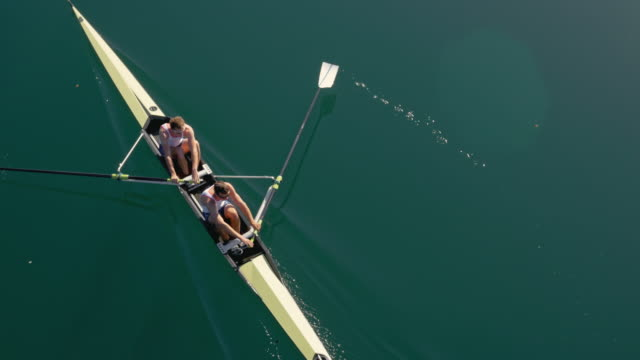 aerial team of rowers in a coxless pair gliding across a sunny lake - rowing stock videos & royalty-free footage