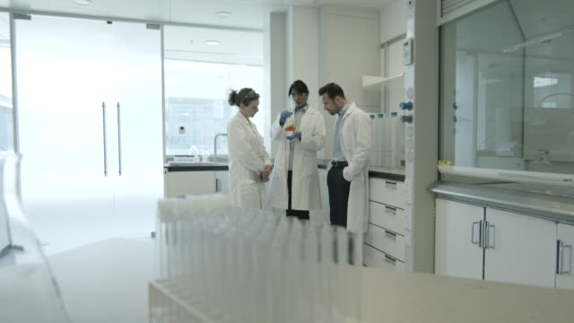 stockvideo's en b-roll-footage met team of scientists discussing liquid experiment - wide shot
