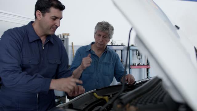 stockvideo's en b-roll-footage met team van senior en volwassen monteurs werken onder de motorkap van een auto tijdens het controleren van de computer lezingen in een auto reparatie winkel - motorkap