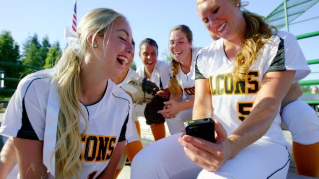 vídeos y material grabado en eventos de stock de ms team of smiling and laughing female softball players on bleachers looking at smartphone before game - sófbol