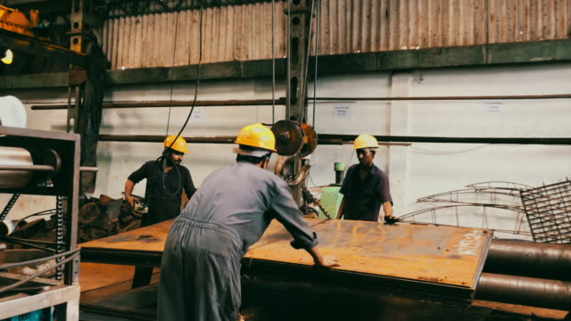 team of steel factory worker using a crane to lower the steel plates - foundry stock videos & royalty-free footage
