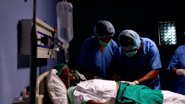 Team of surgeons doing a surgery in hospital, Delhi, India
