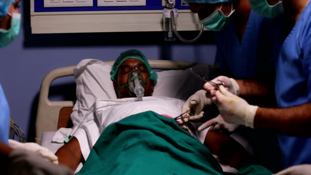 team of surgeons doing a surgery in hospital, delhi, india - surgical mask stock videos & royalty-free footage