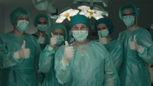vídeos de stock e filmes b-roll de team of surgeons in operating room showing thumbs up - doctor