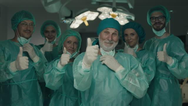 vídeos de stock e filmes b-roll de team of surgeons in operating room showing thumbs up - atitude