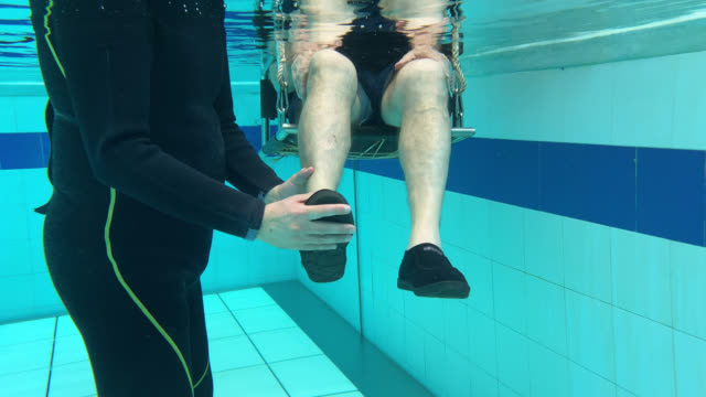 team of therapists working with disabled man on chair during hydrotherapy - hydrotherapy stock videos & royalty-free footage