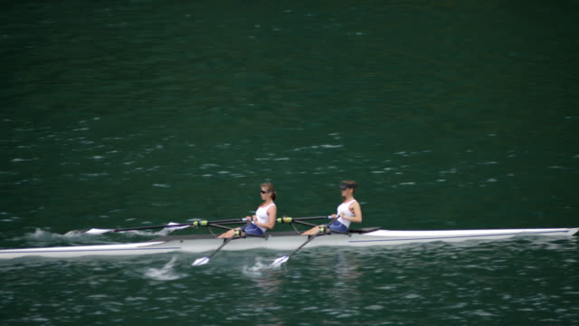 team of two female athletes sculling on a lake - sculling stock videos & royalty-free footage