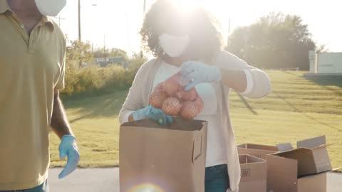vídeos y material grabado en eventos de stock de equipo de voluntarios que ensamblan alimentos donados durante la conducción de alimentos - voluntario