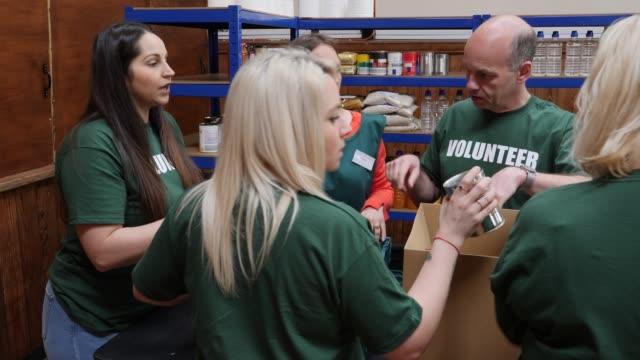 4K: Team of Volunteers sorting food into boxes in a Food Bank