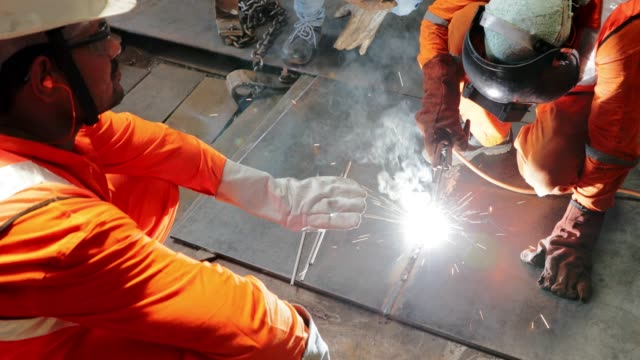 team of welders working together on a steel plate - welding stock videos & royalty-free footage