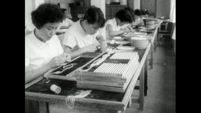 team of women string cultured pearls in pearl farm; 1959 - workbench stock videos & royalty-free footage