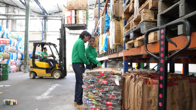 Team of workers at a recycling center looking at a clipboard and another person operating a forklift truck at the background