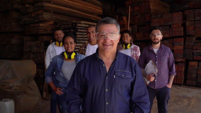 team of workers at a wood factory all facing camera smiling with supervisor in front - labor union stock videos & royalty-free footage