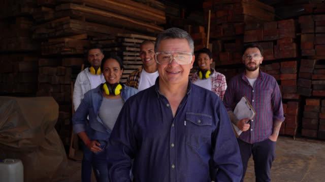 stockvideo's en b-roll-footage met team van werknemers in een houtfabriek alle geconfronteerd met camera glimlachend met supervisor aan de voorkant - vakbond