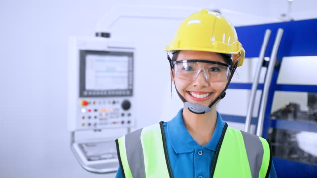 team of workers engineer and factory worker cnc lathe machine. mechanical workers working on milling machine. the technicians wearing protective glasses and helmet when operating the machine for safety precaution. - production line stock videos & royalty-free footage