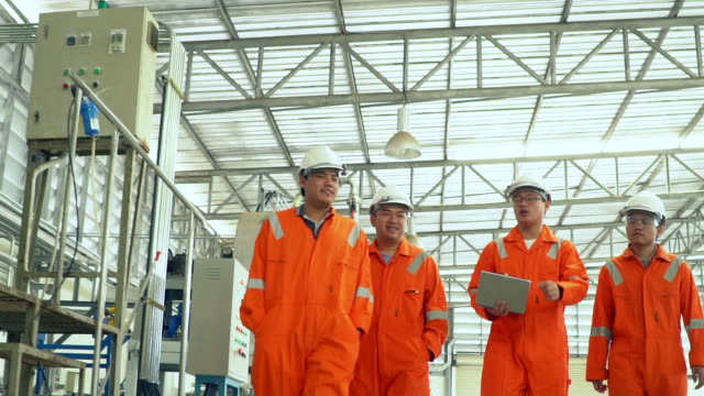team of workers walking and discussi in fuel plan industrial background - health and safety stock videos & royalty-free footage