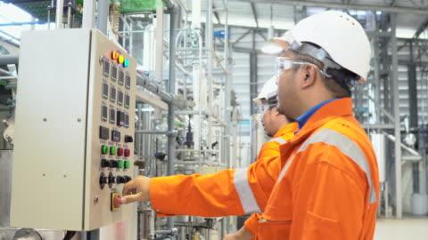 team von arbeitern zu fuß und diskutiereni in kraftstoffplan industrielle hintergrund - manufacturing occupation stock-videos und b-roll-filmmaterial