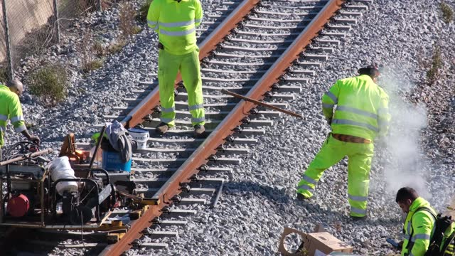 team of workers welding, cutting, repairing, assembling taking train tracks on a sunny day outside of barcelona in times of a pandemic with covid 19 masks - workbench stock videos & royalty-free footage