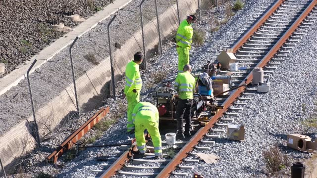 team of workers welding, cutting, repairing, assembling taking train tracks on a sunny day outside of barcelona in times of a pandemic with covid 19 masks - installing stock videos & royalty-free footage