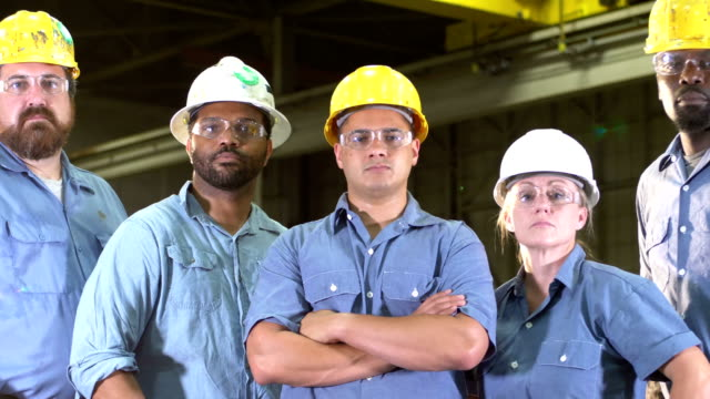 team of workers with hard hats, safety glasses, serious - manufacturing occupation video stock e b–roll