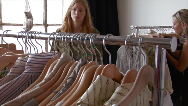 team of young fashion designers and stylists looking through racks of clothes - 2000s style点の映像素材/bロール
