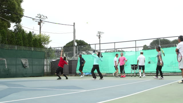 team practicing serve on tennis court - テニス点の映像素材/bロール