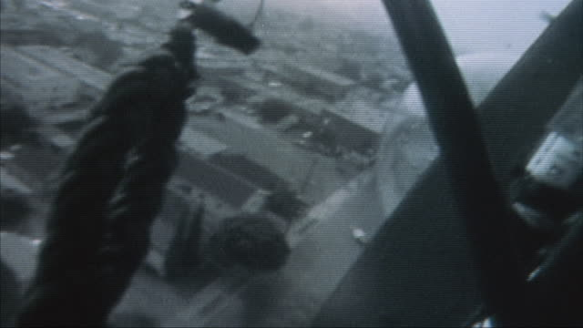 A SWAT team rides in a police helicopter then descends ropes to the rooftops below.