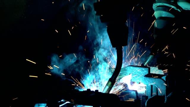 Team robot are welding steel part in factory