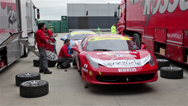 team rossocorsa mechanics fitting wet weather tyres on a ferrari 458 at silverstone racetrack, england. - silverstone stock videos & royalty-free footage