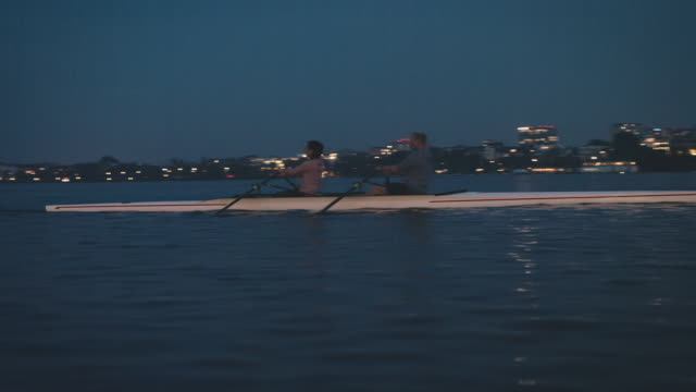 team rowing boat in river at night - sculling stock videos & royalty-free footage