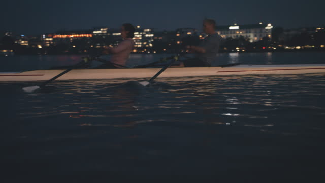 team rowing rowboat in river at night - sculling stock videos & royalty-free footage