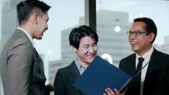 hr team- thai businessman showing document for senior manager and team with positive emotion - recruit stock videos & royalty-free footage