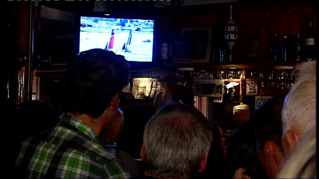 Celebrations in Lymington ENGLAND Hampshire Lymington INT People gathered in bar watching America's Cup 2013 on television screen / people cheering...
