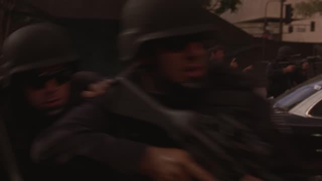 A SWAT team with machine guns and bulletproof vests maneuvering through a gunfire battle.