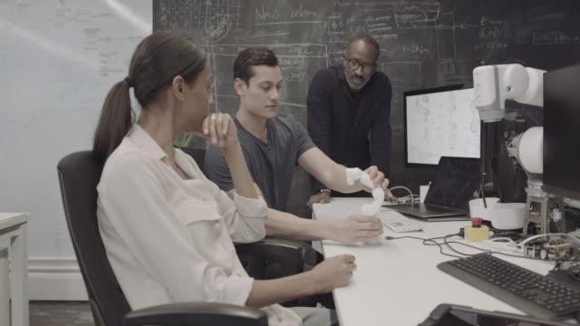 team working on robotic arm design in office - プロトタイプ点の映像素材/bロール