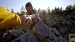 Teammate helping hiker to reach summit. Couple hiking in Switzerland, hand reach out to help female hiker reach the summit. A helping hand concept