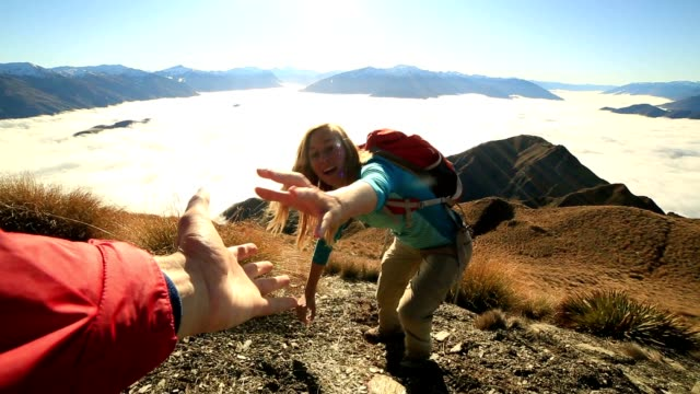 teammate helping hiker to reach summit - mountain climbing stock videos & royalty-free footage