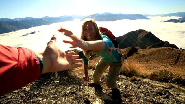 Teammate helping hiker to reach summit