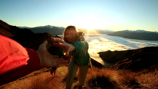 teammate helping hiker to reach summit - new zealand stock videos & royalty-free footage