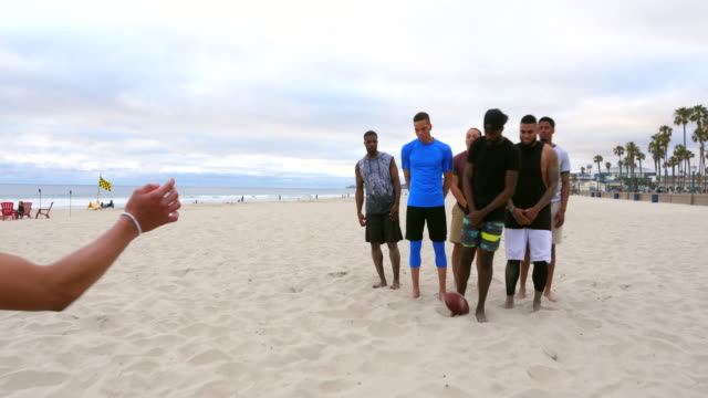 ms teammates celebrating touchdown during beach football game - drive ball sports stock videos & royalty-free footage