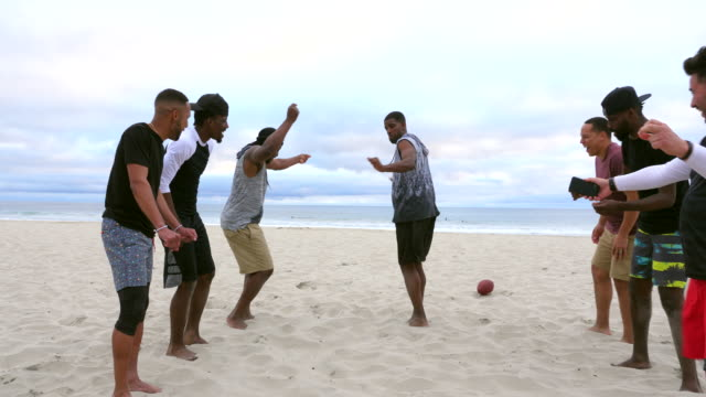 ms teammates doing celebration dance after winning touch football game on beach - drive ball sports stock videos & royalty-free footage