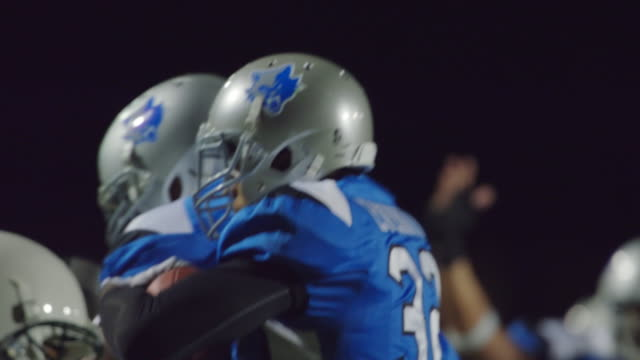 CU SLO MO. Teammates embrace and pat helmets after touchdown play in professional football game.