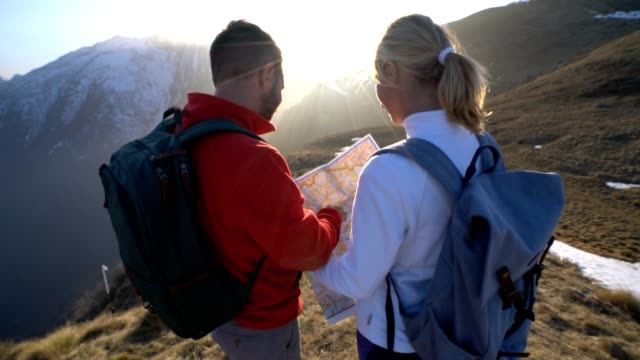 Teammates hiking in Switzerland looking at map