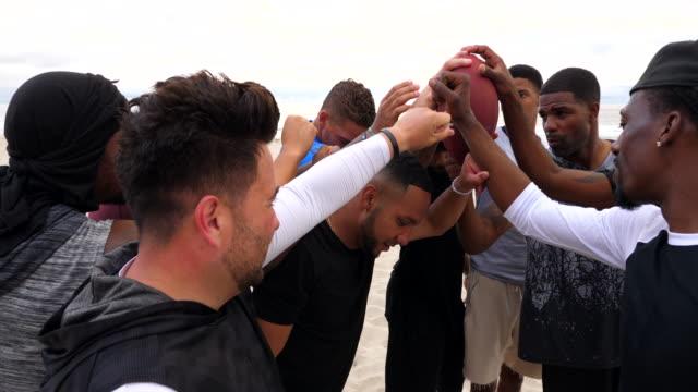 vídeos de stock e filmes b-roll de ms teammates in huddle during football game on beach - 30 39 anos