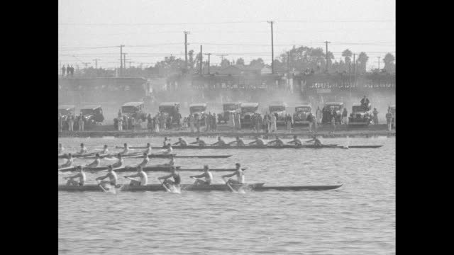stockvideo's en b-roll-footage met vs teams of eight rowers compete in the men's eight competition at long beach marine stadium during the 1932 summer olympic games / crowds look on... - long beach californië