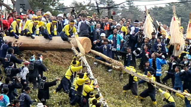Teams of men straddled a thick log and then held on for dear life as it was launched downhill during the climax to the famed Onbashira festival held...
