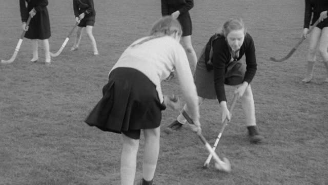 montage teams playing field hockey, pedestrians walking through park and children playing on park equipment / united kingdom - field hockey stock videos and b-roll footage