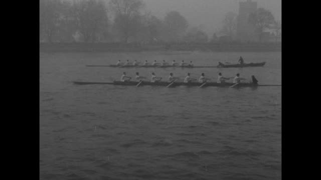 vídeos de stock, filmes e b-roll de teams rowing on river with snow bank beyond during the annual boat race on the thames river / riverbank with building at rear / people bundled up... - chuva congelada