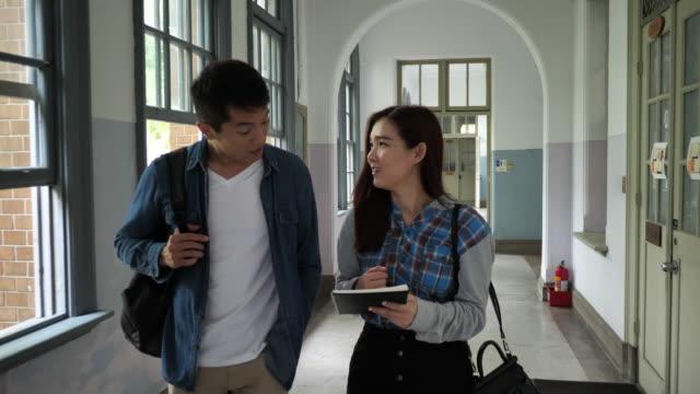 大学でのチームワーク - 学生は講義の前に互いに助け合う - east asian ethnicity点の映像素材/bロール