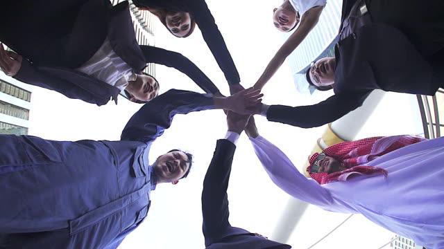 stockvideo's en b-roll-footage met teamwork concepten. mensen uit het bedrijfsleven met diversiteit in leeftijd, ras, geslacht, regio toetreding samen handen. slow-motion. - mixed race person
